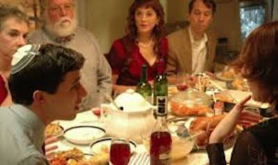 Jewish family talking around a table laden with delicious food